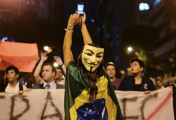 A demonstrator wearing a Guy Fawkes mask takes photos on her mobile phone during a protest in central Rio de Janeiro