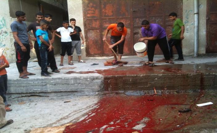 Si lava il sangue lungo il muro perimetrale dell'ospedale di Shifa (Foto: Michele Giorgio)