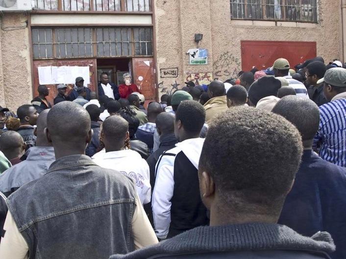 """Immigrati che attendono di essere ricevuti fuori il centro sociale di Caserta """"Ex Canapificio""""."""