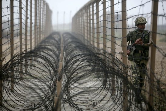 India's BSF soldier patrols near fenced border with Pakistan in Suchetgarh