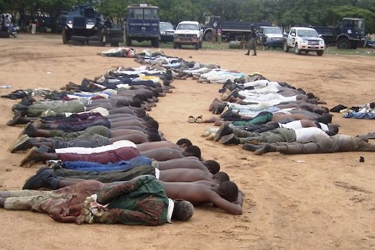 Members of an local Islamic group lie on the ground at a police station after their arrest in the northeastern city of Bauchi