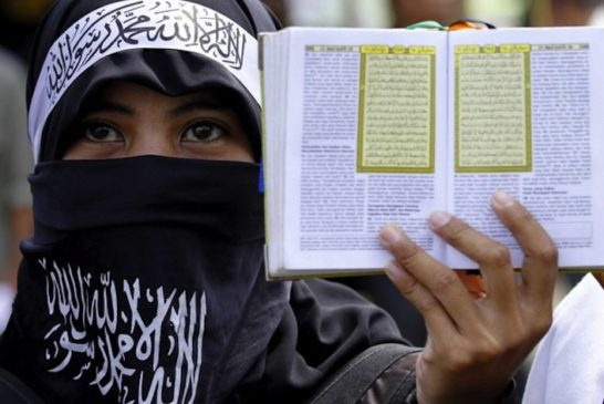 member of the Islamic group Hizbut Tahrir Indonesia carries a Koran during a protest in Makassar, South Sulawesi September 4, 2010