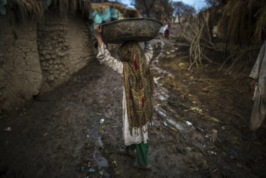 An Afghan girl carries a basin as she walks toward her makeshift shelter in a slum on the outskirts of Islamabad