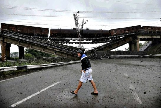 A man walks past a destroyed railroad bridge which fell over a m