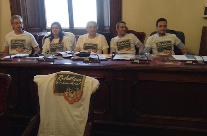 Membri del consiglio comunale di Piacenza indossano la maglietta con su scritto: «Ridateci le merendine».