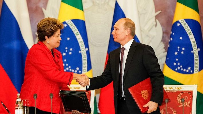 La Rousseff stringe la mano al presidente russo Vladimir Putin, grande alleato internazionale del Brasile. I due Paesi hanno nel luglio scorso siglato un accordo (insieme a Cina, India e Sudafrica) che prevede la nascita di un sistema monetario alternativo al dollaro.
