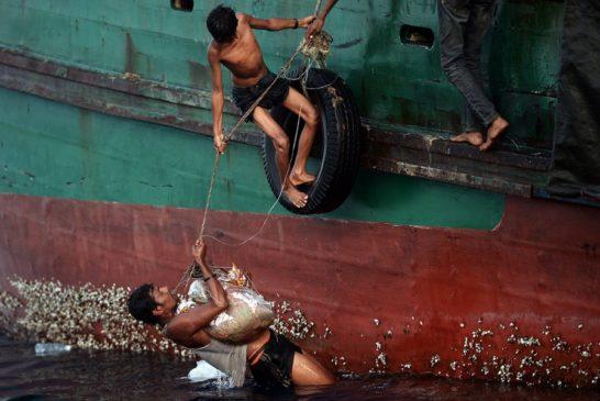 Migranti Rohingya cercano di portare a bordo di un barcone abbandonato in mare dagli scafisti il cibo lanciato dagli elicotteri dell'esercito thailandese