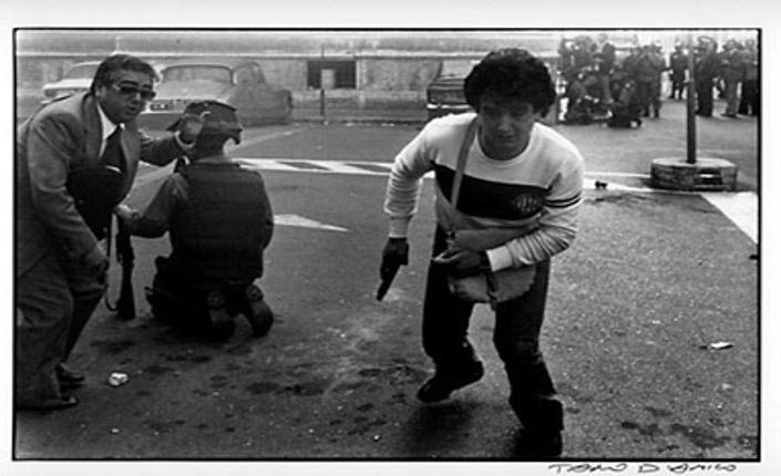 Foto di Tano D'amico raffigurante l'agente Giovanni Santone in borghese armato durante gli scontri. Alla sua destra un funzionario e un agente in divisa