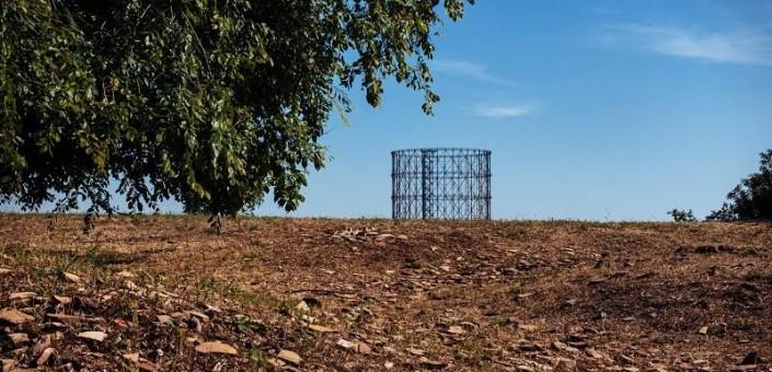 Una veduta di Monte Testaccio in cui si vedono i frammenti di anfora, testimonianza del passato, il gasometro simbolo della città moderna e la fronda di un albero segno della natura che si è riappropriata della città