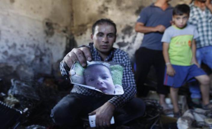 Un parente mostra la foto del piccolo Ali, ucciso nel rogo della sua casa appiccato da coloni israeliani