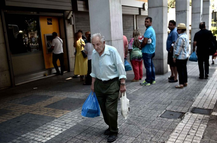 2048x1536-fit_a-athenes-grece-le-30-juin-2015-un-vieil-homme-marche-passe-devant-une-banque-ou-une-file-s-est