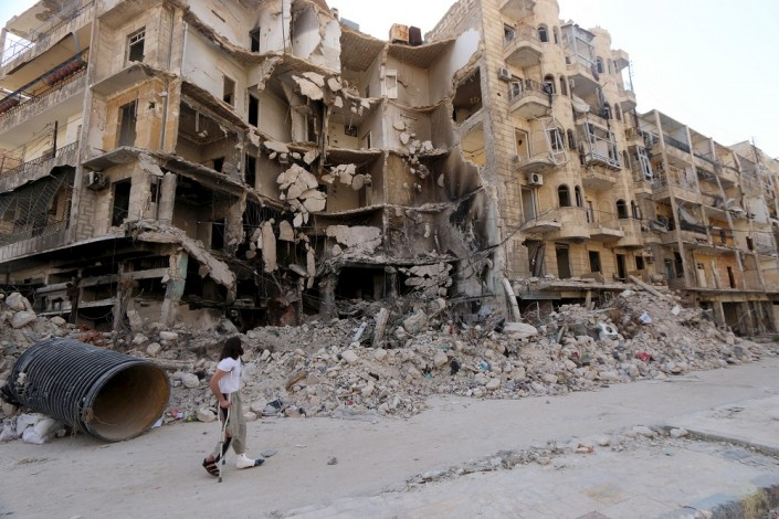 A man walks with the aid of a crutch past damaged buildings in the old city of Aleppo