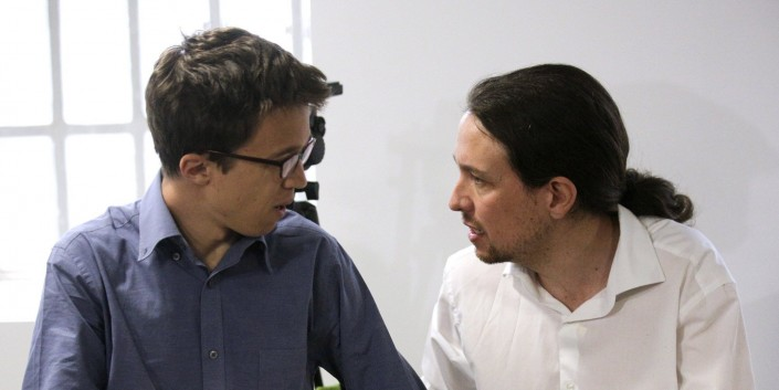 Iglesias, leader of Spain's Podemos (We Can) party, talks with campaign director Errejon during a meeting with candidates for upcoming regional elections in Madrid