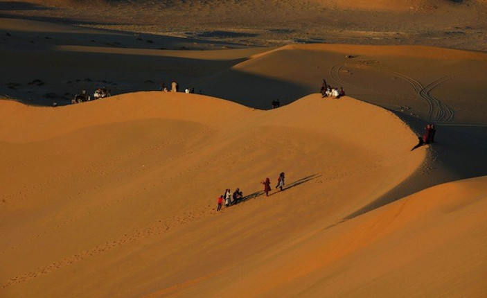 Migranti attraversando il deserto libico