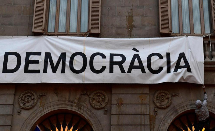 Barcellona. Marcia contro il referendum. Un uomo tenta di togliere lo striscione, con su scritto Più Democrazia, posto sulla facciata del Municipio della città.